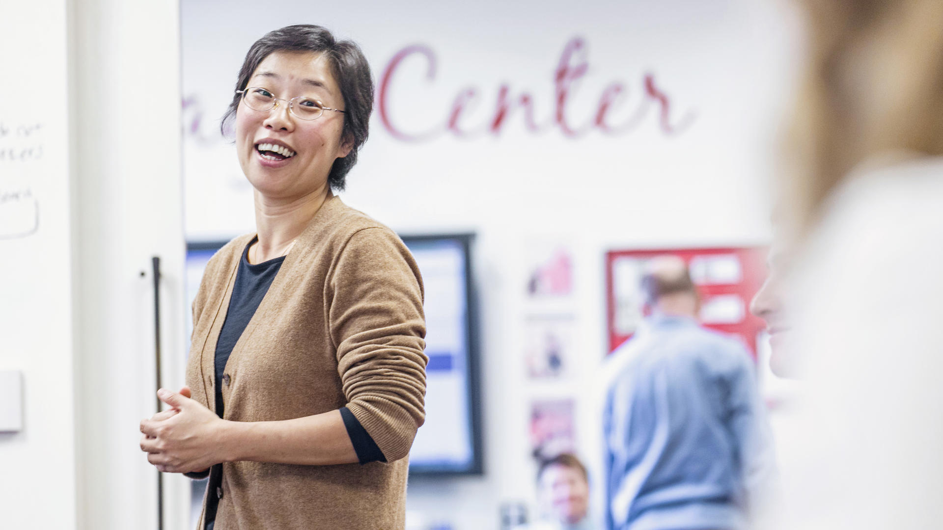 An Asian woman in a tan sweater laughs with students