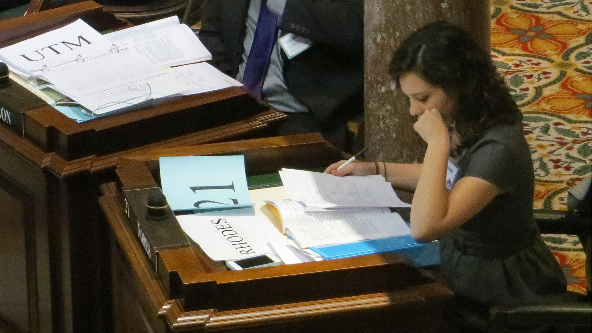 a female student studies legislative papers at a desk