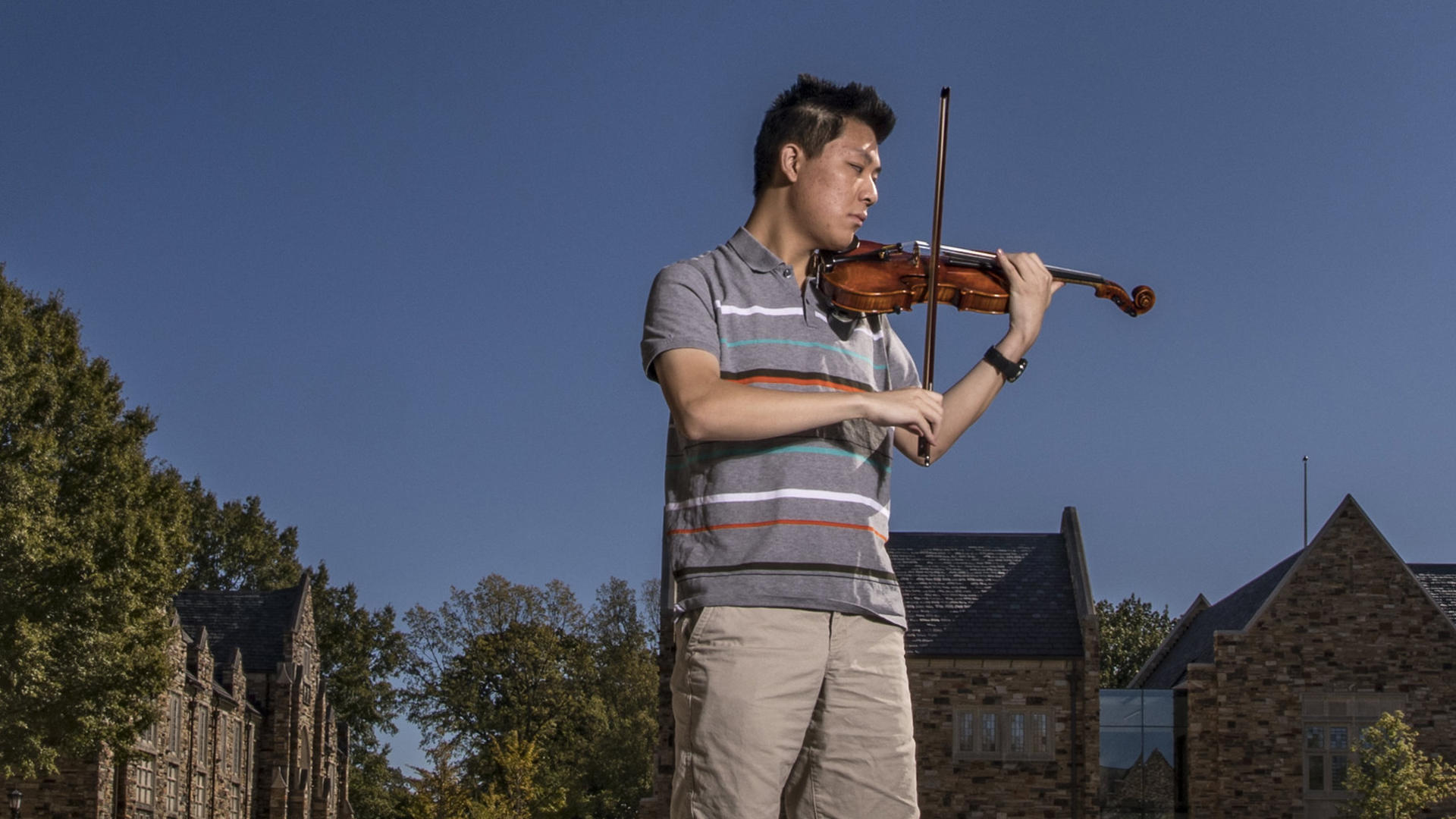 a young Asian man plays the violin