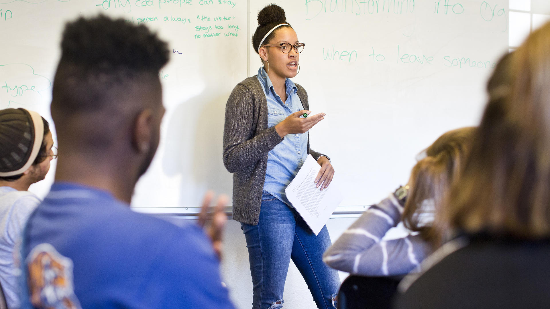 a young African American woman leads a class