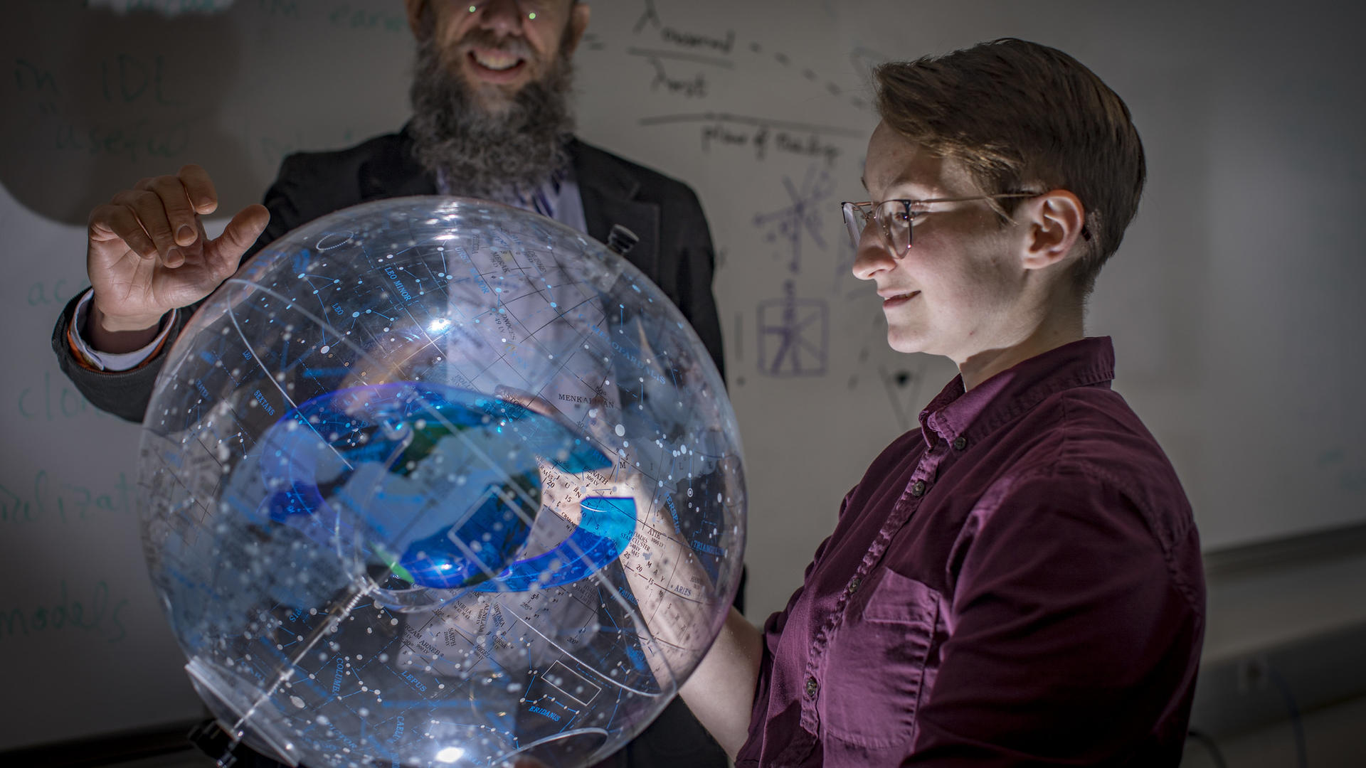 A professor and student look through a model of the galaxy