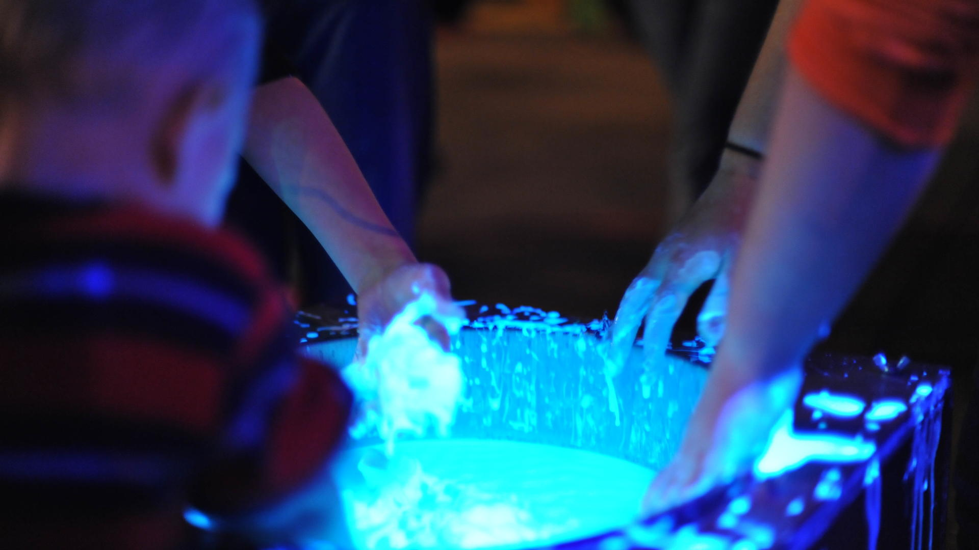 Physics students dip hands in neon blue fluid