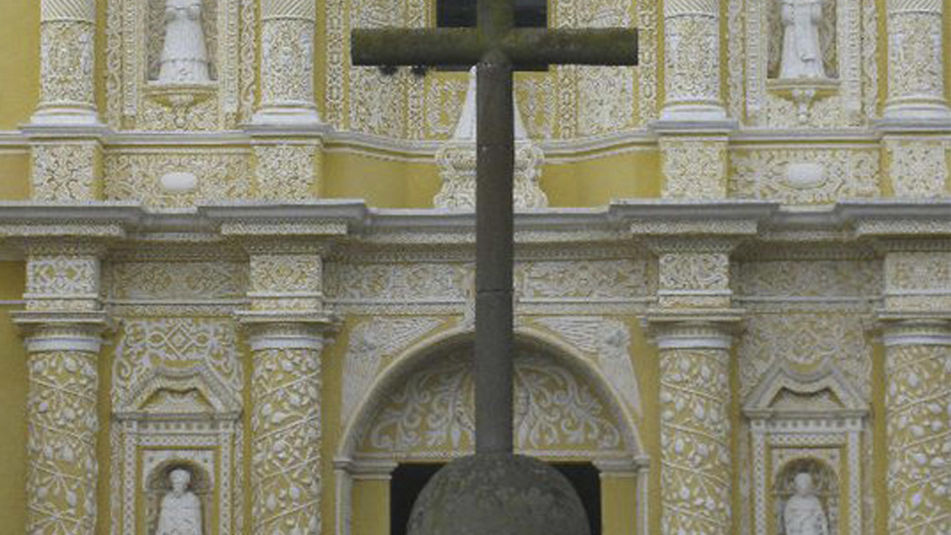 a cross outside an ornate church