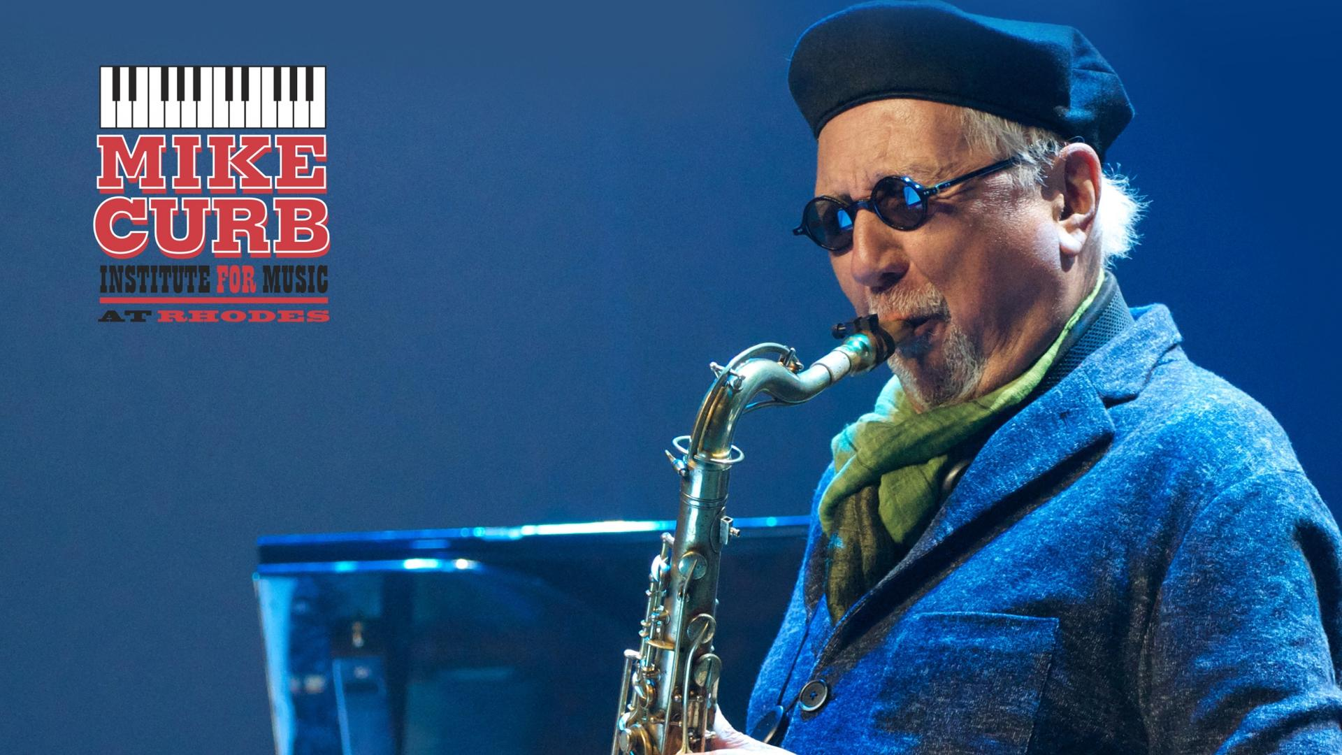 A man in sunglasses and a flatcap plays the tenor sax.