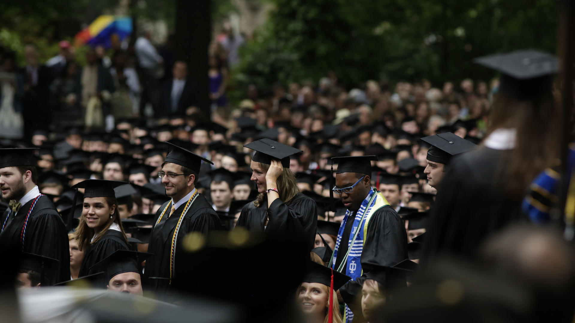 A procession of graduates in their caps and gowns make their way among the rows of seated graduates