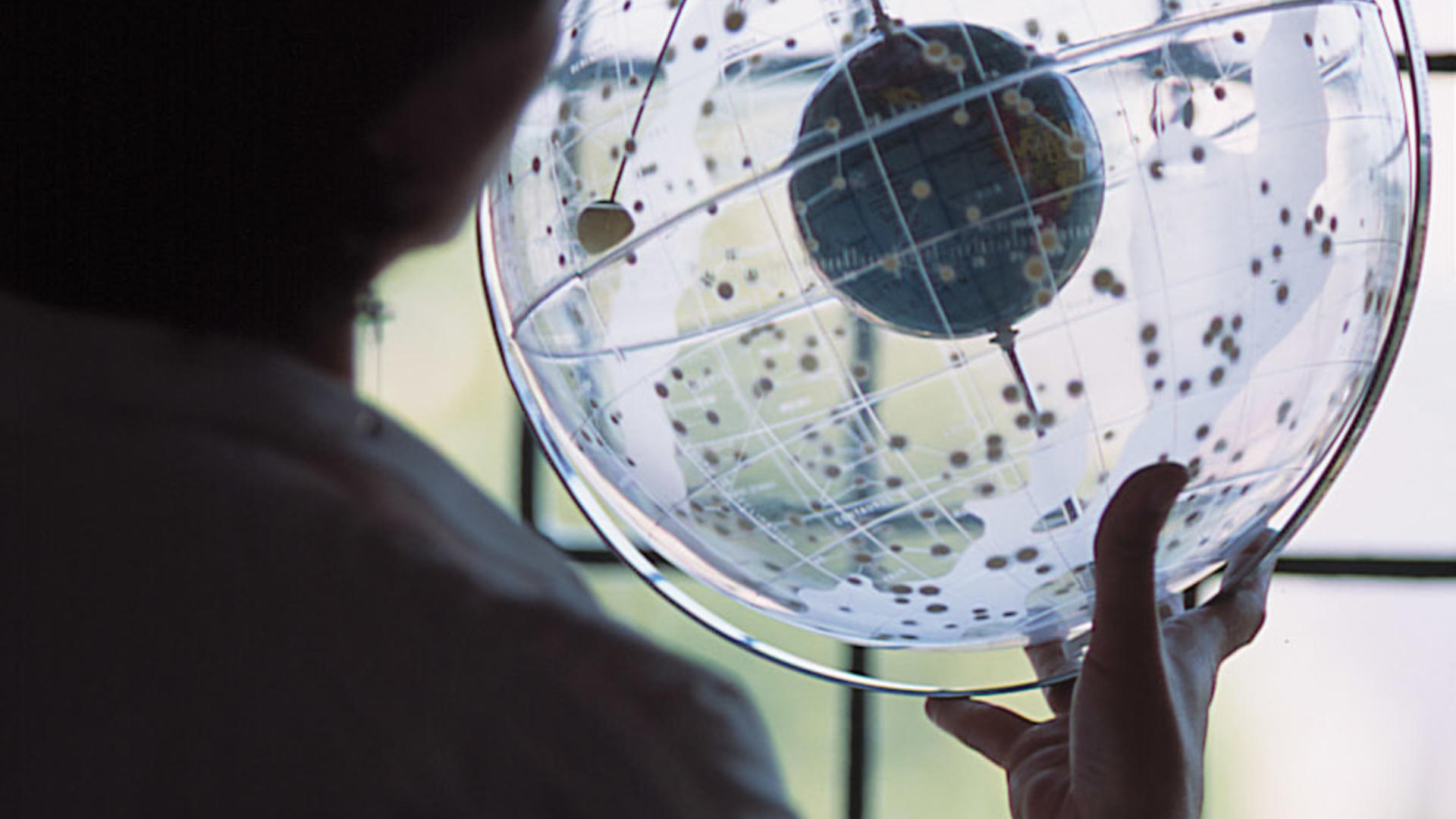 a student examining a clear globe