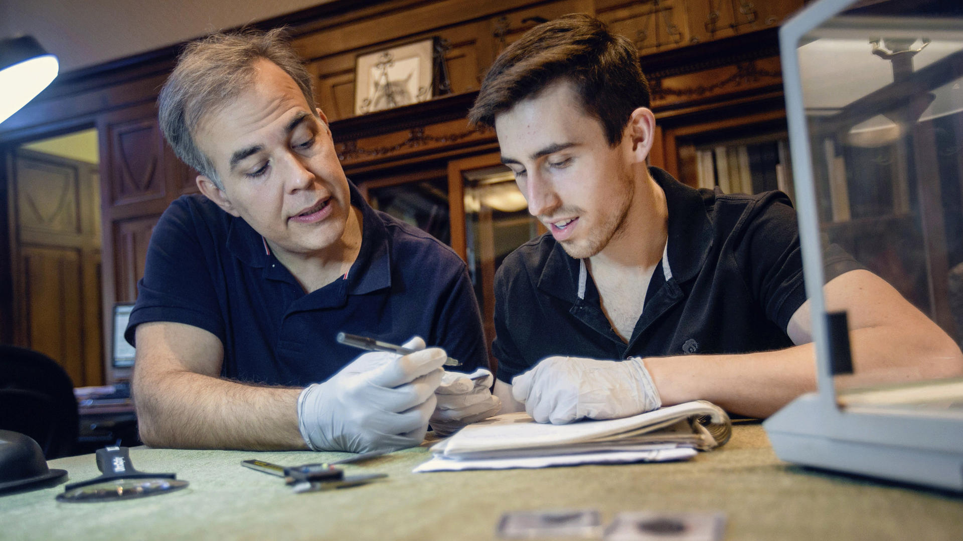 a professor and a student examining an artifact