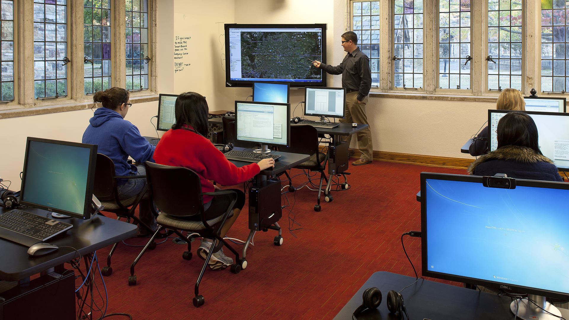A professor points at a projected map while students sit in from of computers in the language lab