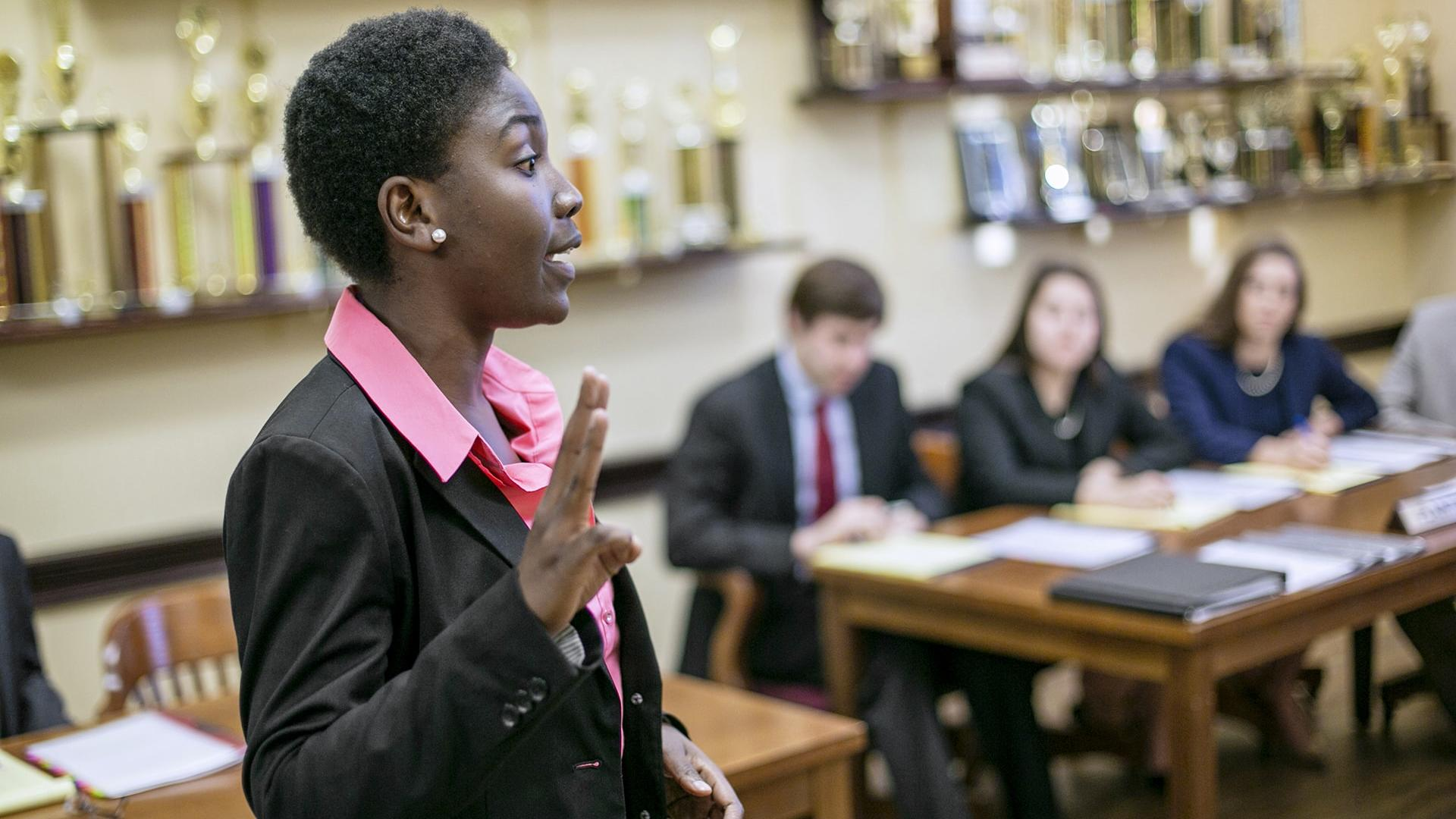 a young woman in a suit speaks before students at a desk in a room lined with trophies