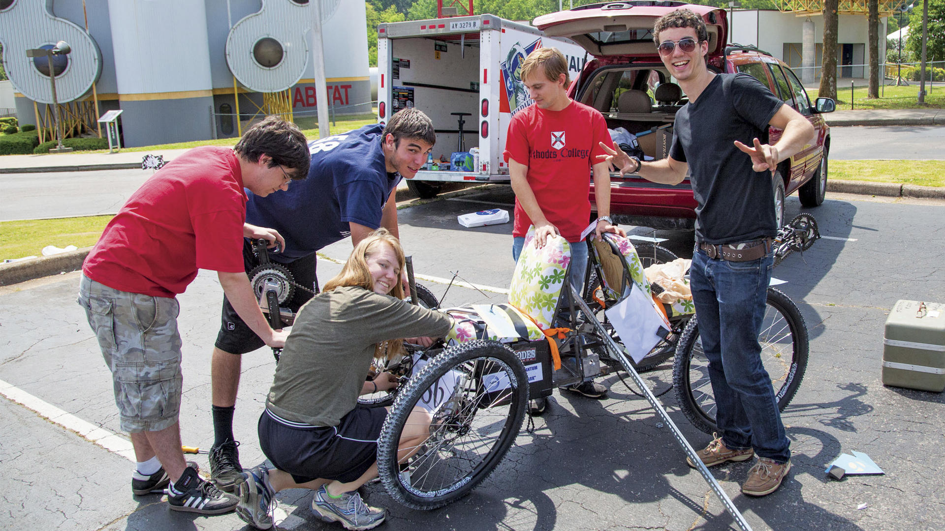 Students tinker with a tricycle in front of a silo that says U.S. space camp