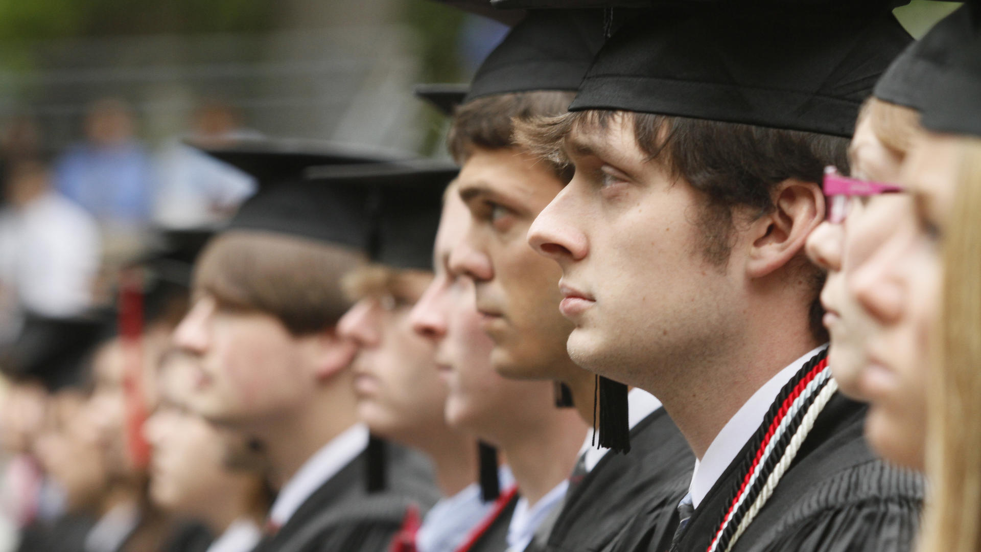 Students in caps and gowns are shown in profile