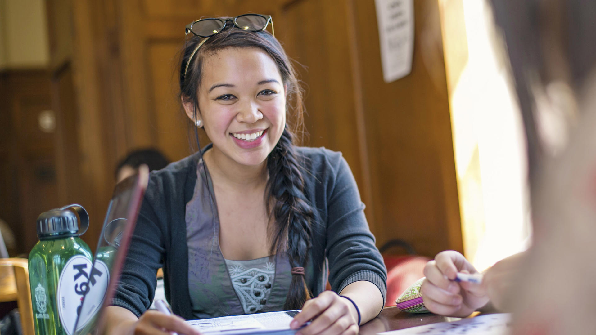 a student smiling and studying in the refectory
