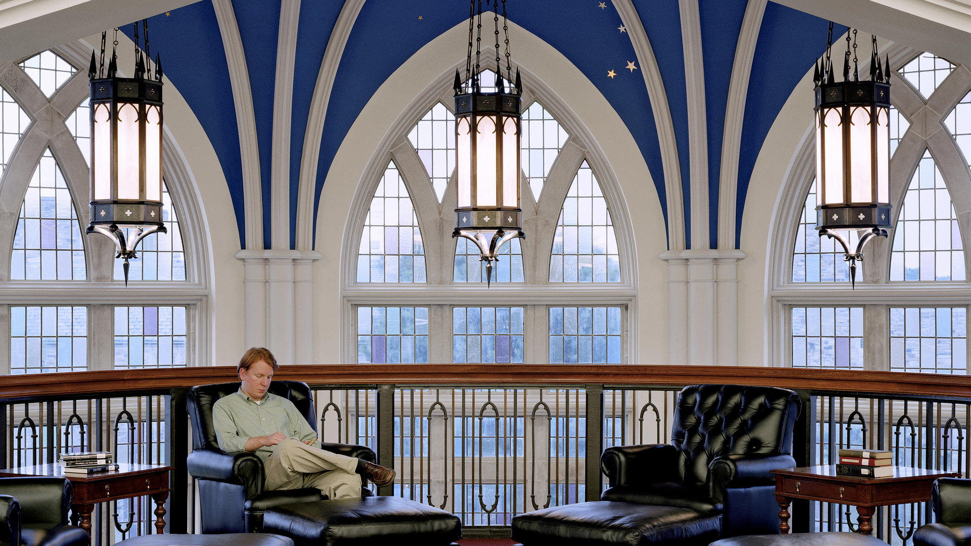 A student lounges in a blue armchair below the blue apse and three lanterns