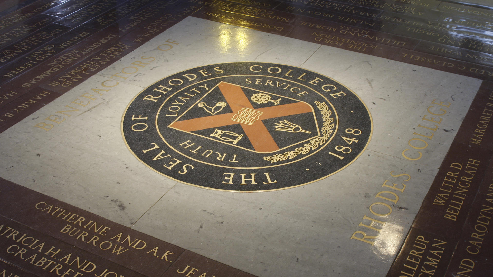 The seal of Rhodes College inlayed in the floor of Palmer Hall. If a student walk across it, the legend says that they will ever graduate