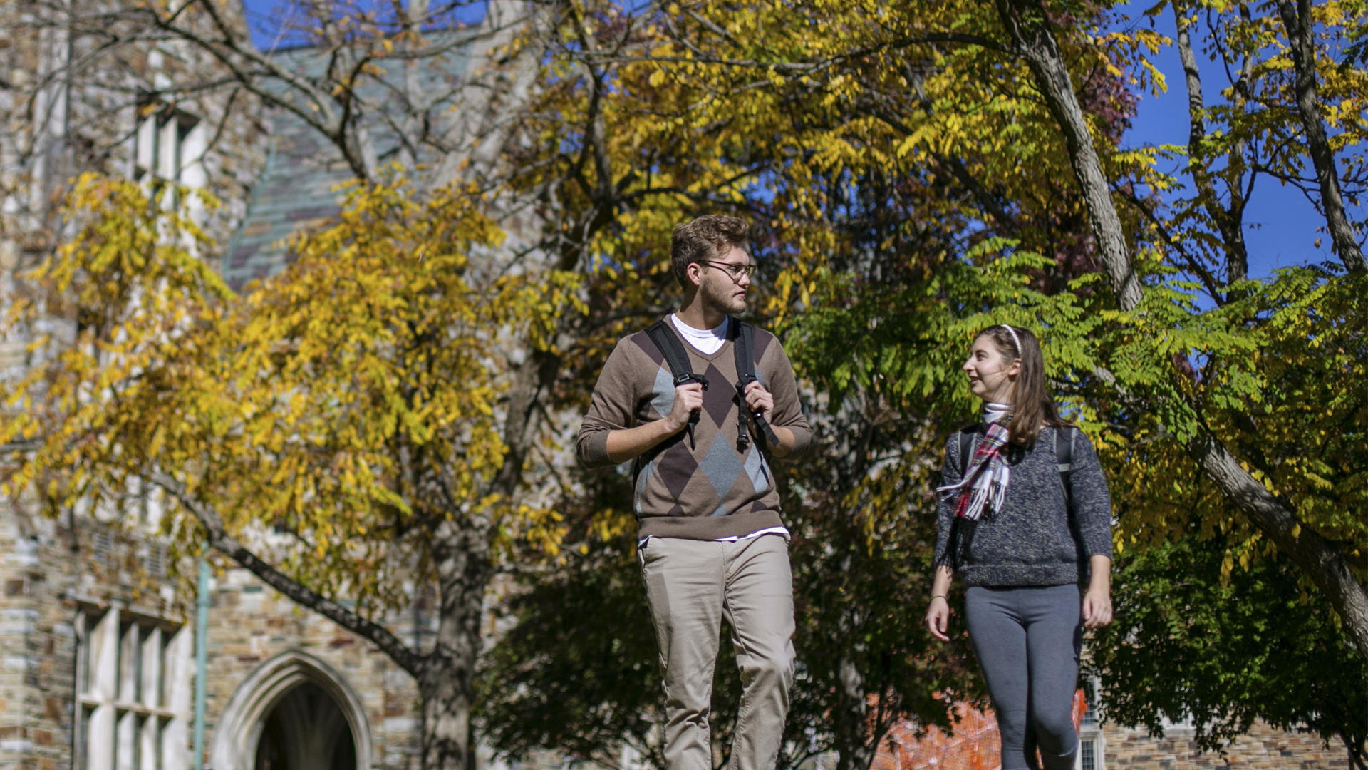 two students walking outside on a sunny fall day