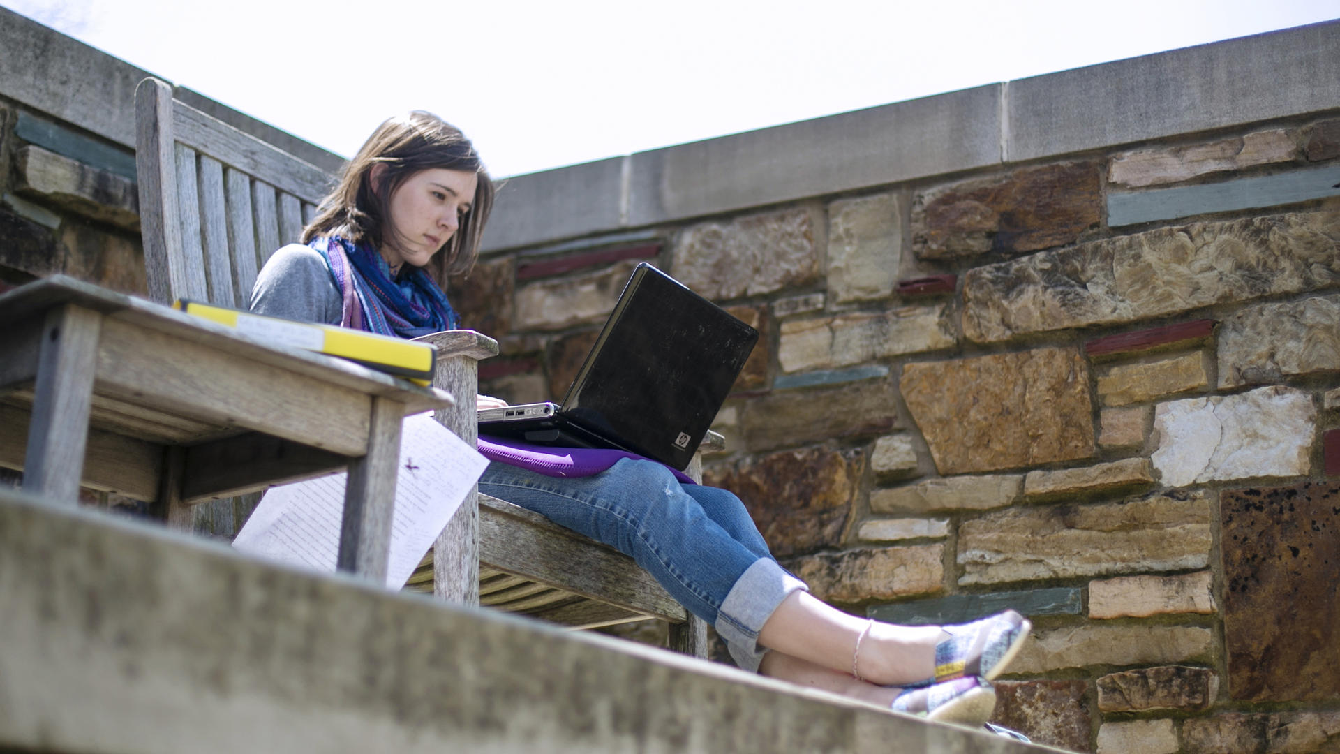 A student sitting on a bench with a laptop