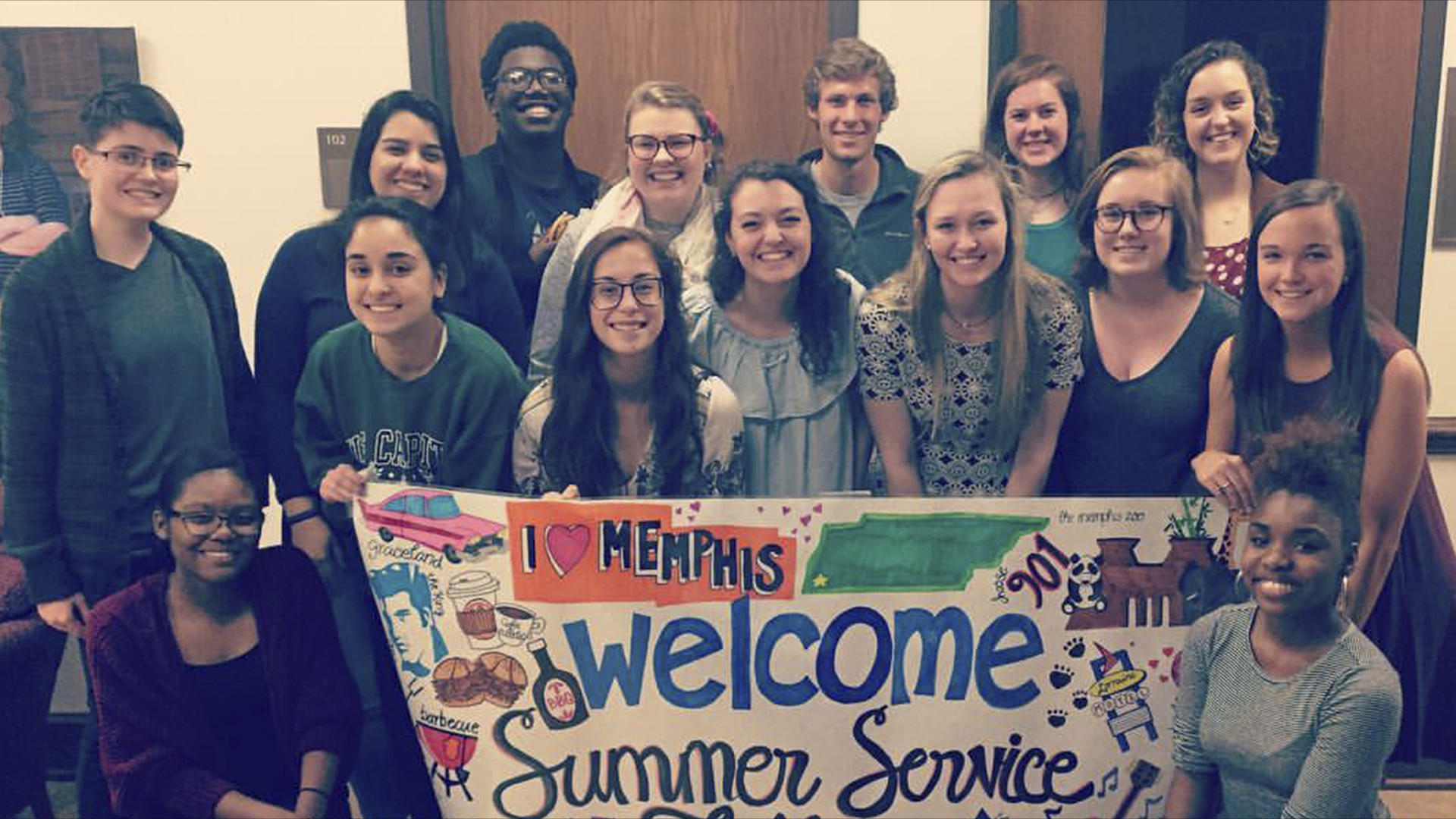 a group of students holding a welcome sign