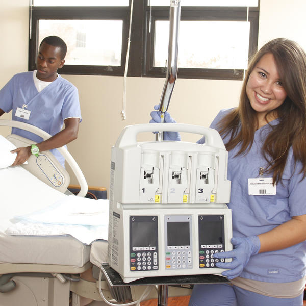 a student standing with a medical machine