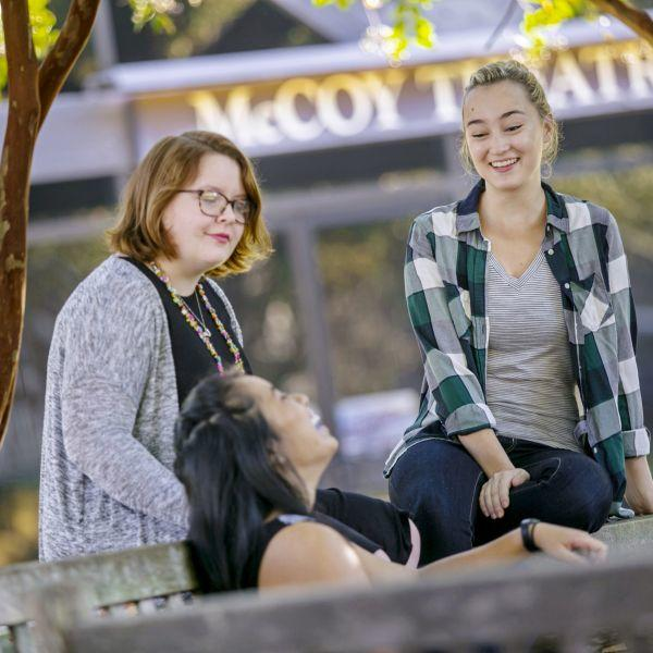 Three students laugh and talk near a bench outside the McCoy Theatre