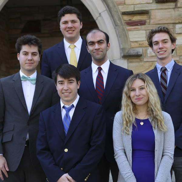 Group of students in professional attire in front of a stone Rhodes building and archway