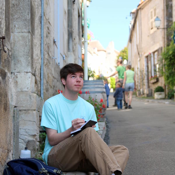 A student sit on a curb on a European street, sketching in a notebook