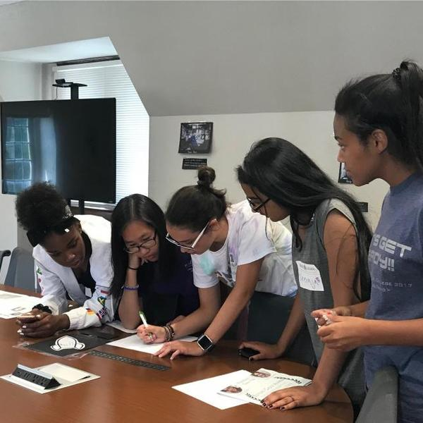 a group of young women studying a document