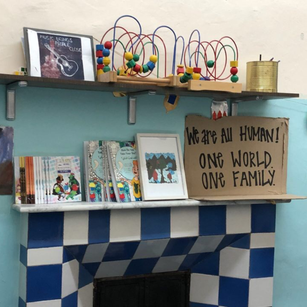 "A shelf on a blue wall covered in books, toys, and a sign that reads: ""We are all human. One world. One family."""