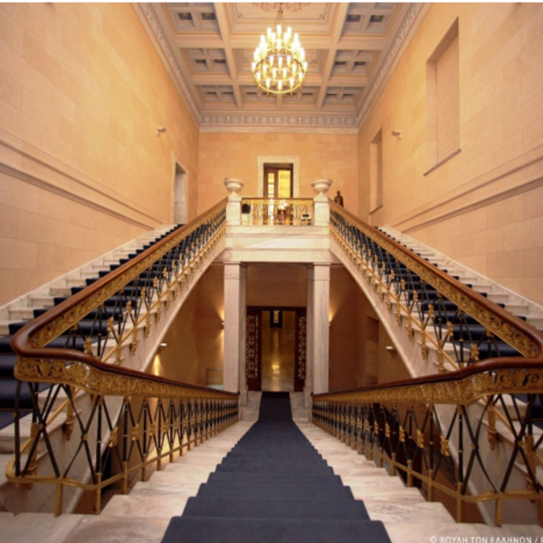 A photo of a hall with two staircases going up each side
