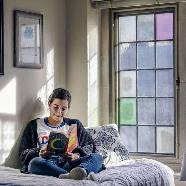 A young woman sits on her bed reading by the light of a stained glass window.