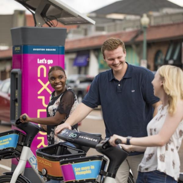 A young man and woman rent bikes from a rideshare station in a small shopping center.