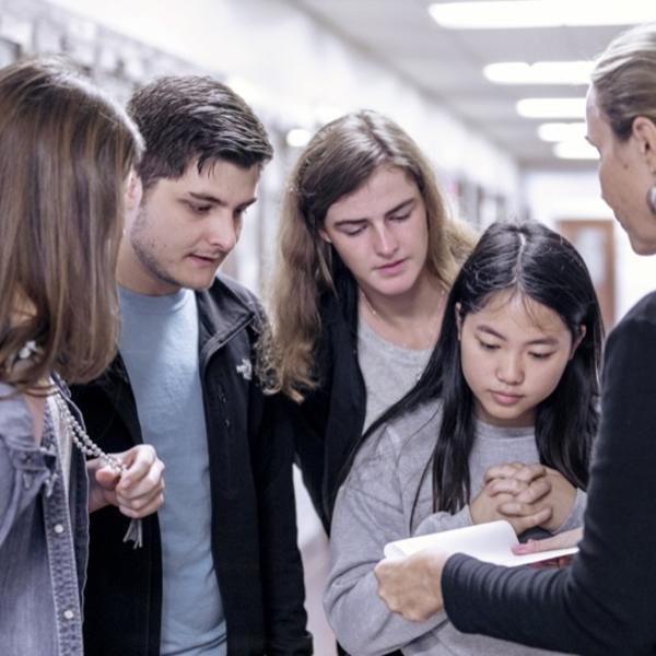 A group of young people on a scavenger hunt huddle around a young woman holding a map