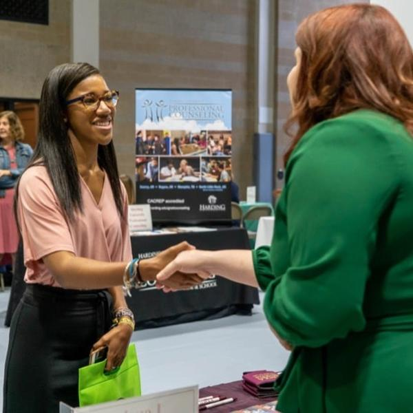 Two women shake hands at a recruiting fair.