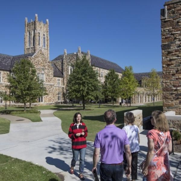 A student in a red and black rugby jersey leads a tour on a beautiful spring morning.