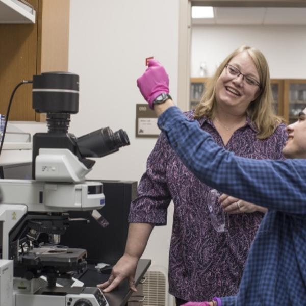A professor and her student examine a lab specimen.