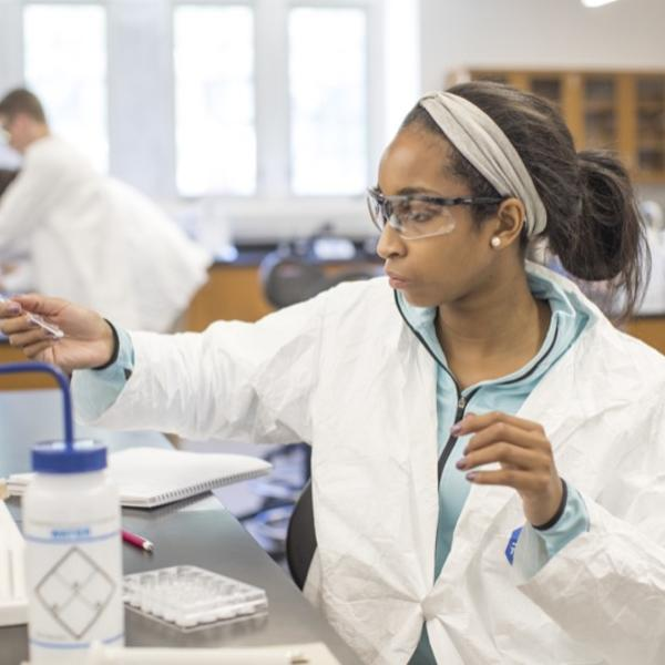 A student in a lab coat adjusts her equipment.