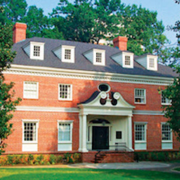 A red brick, three-story colonial style building with white trim.