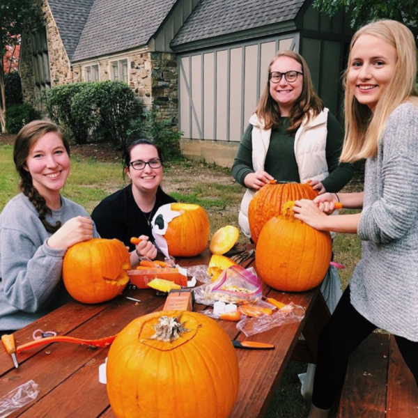 Four young women carve pumpkins in foreground of a sorority house
