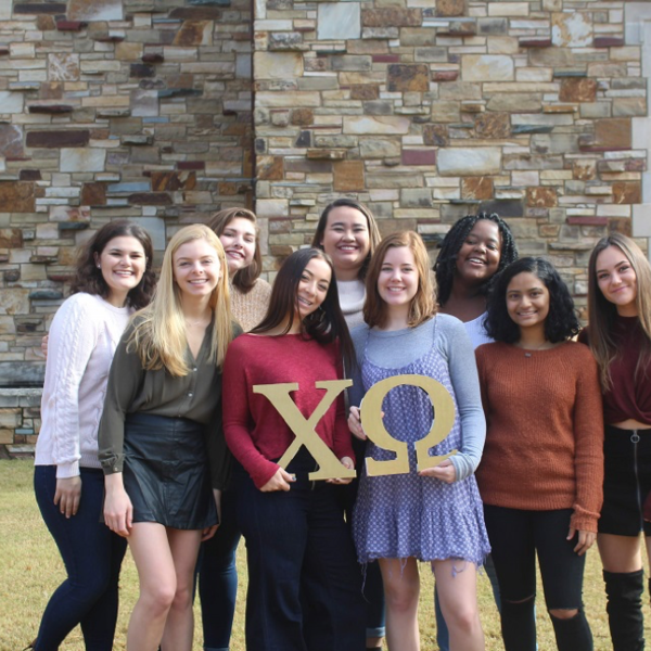 A group of women in foreground of a stone building, holding Chi Omega letters