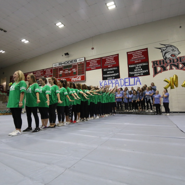 Women in green shirts stand in a dance line in a gym in front of the words Kappa Delta