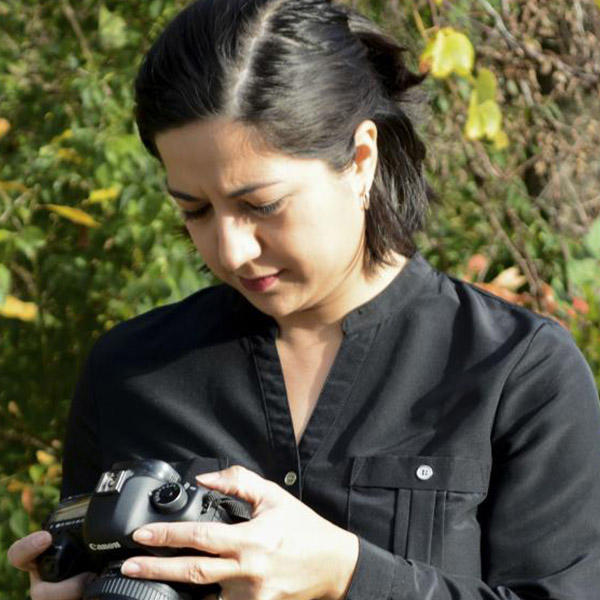 a female with dark hair holding a camera