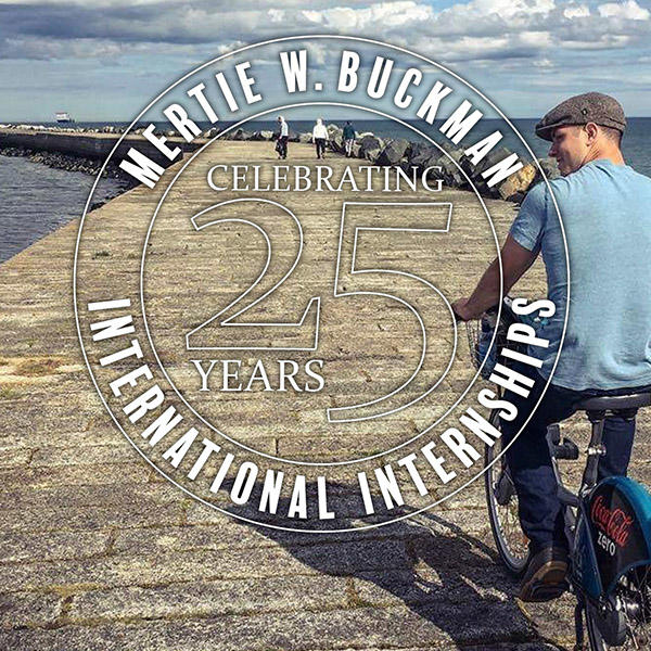 a young man with a hat rides a bicycle on a pier
