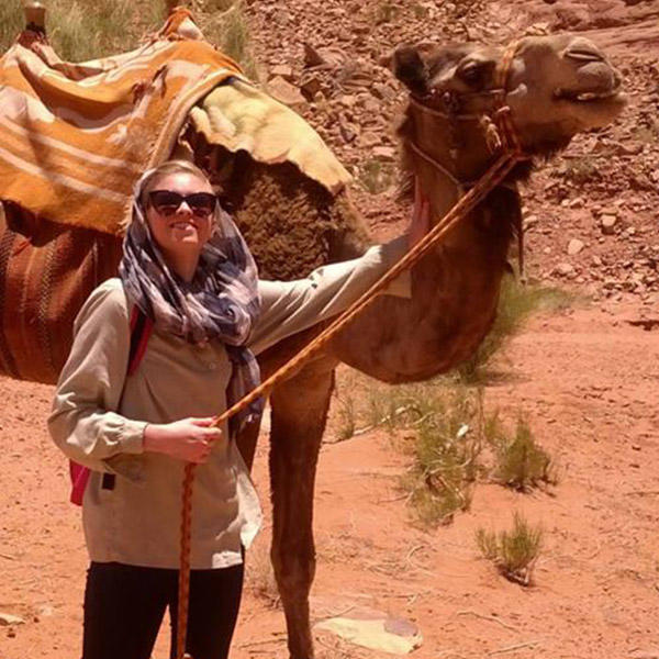 a young woman in a head scarf holds the reins to a camel