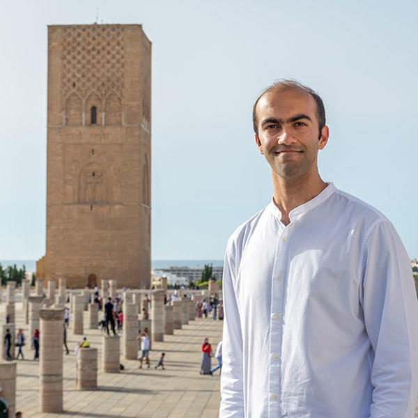 a yoiung man stands in front of a Moroccan tower