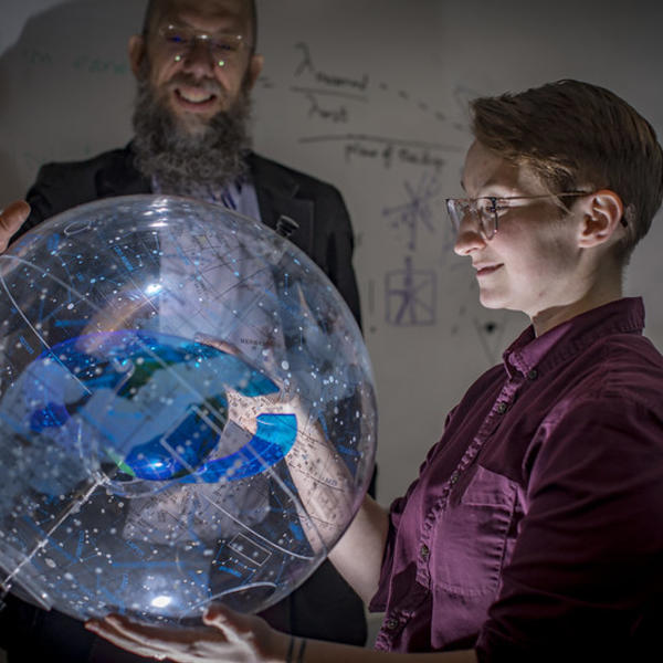 A professor stands behind a clear model of the milky way. Light shines up from beneath the model, onto the face of a student to whom he is explaining it.