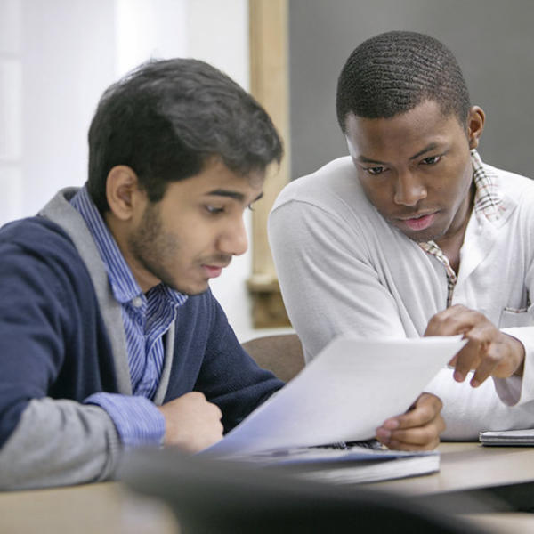 A young man helps a fellow student go over an assignment.