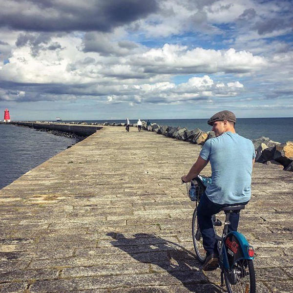 a young man bikes on a quay by the sea