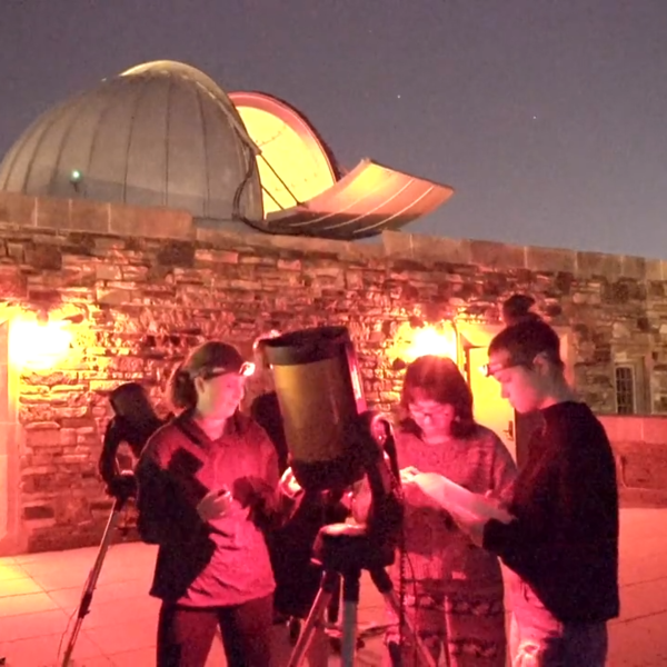 Students on the the astronomy deck gathered around a telescope.