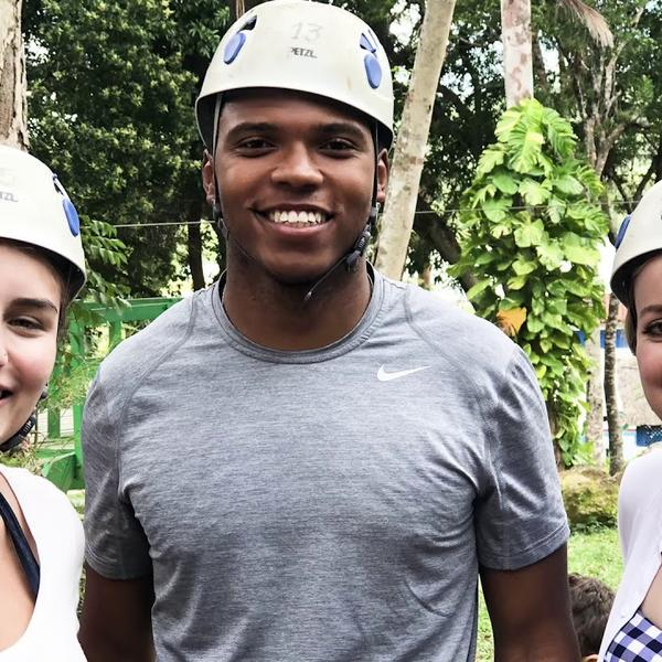Three students in safety helmets pose for a photo with woods in the background.