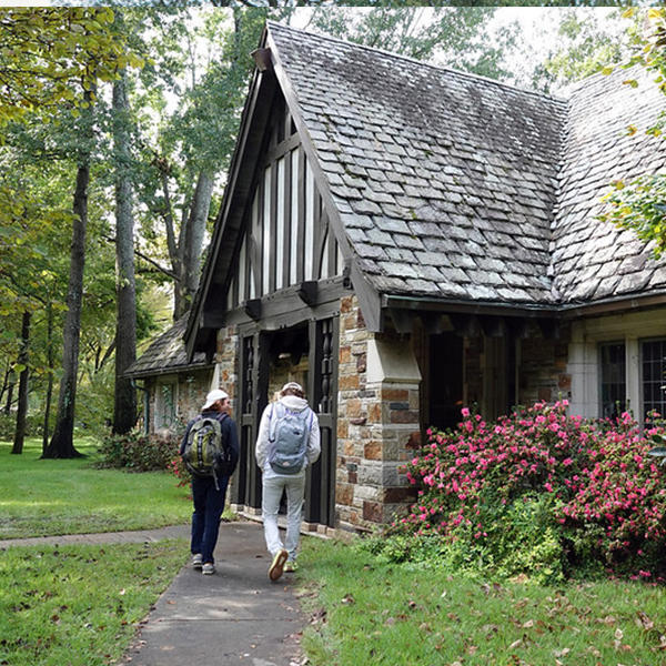 students with backpacks walk to a tudor style building