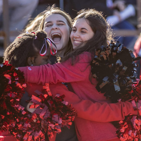 Cheerleaders hug at a football game.
